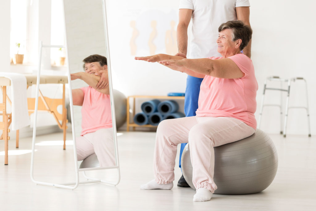 Smiling senior exercising with a physiotherapist at a white gym